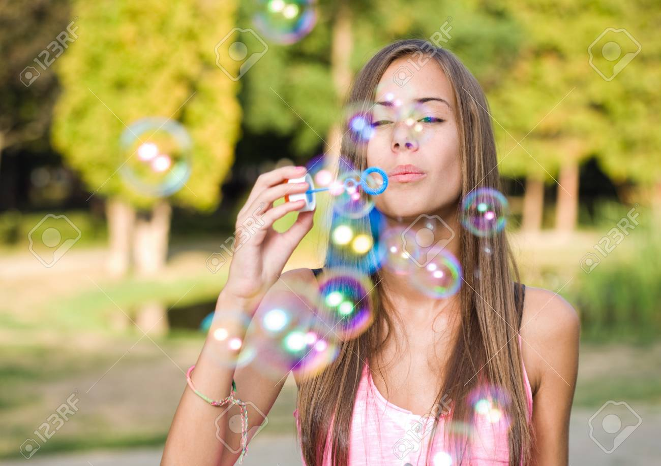 Free the bubbles, portrait of a beautiful young girl having fun outdoors blowing soap bubbles. Stock Photo - 15005494