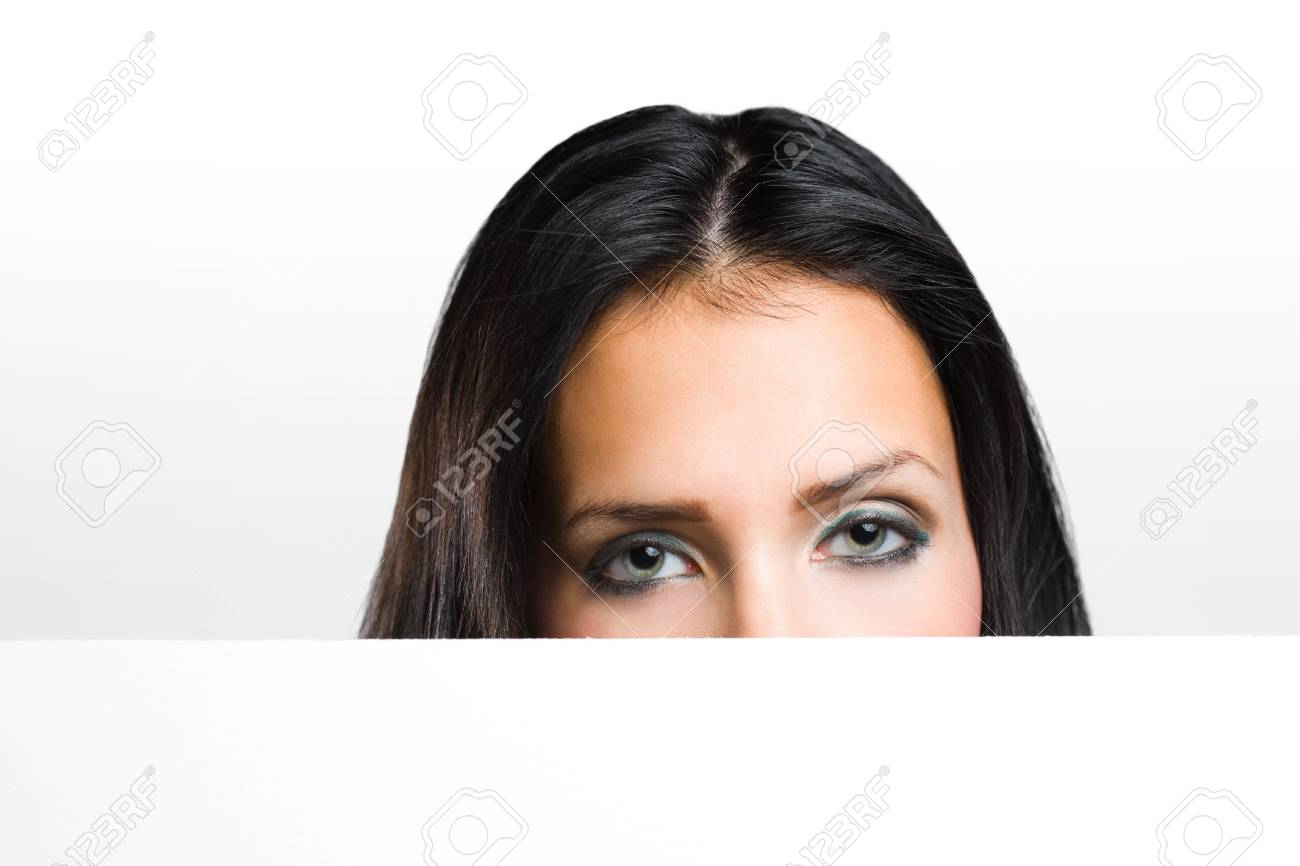 Portrait of a beautiful brunette peeking out from behind blank white banner. Stock Photo - 15896761