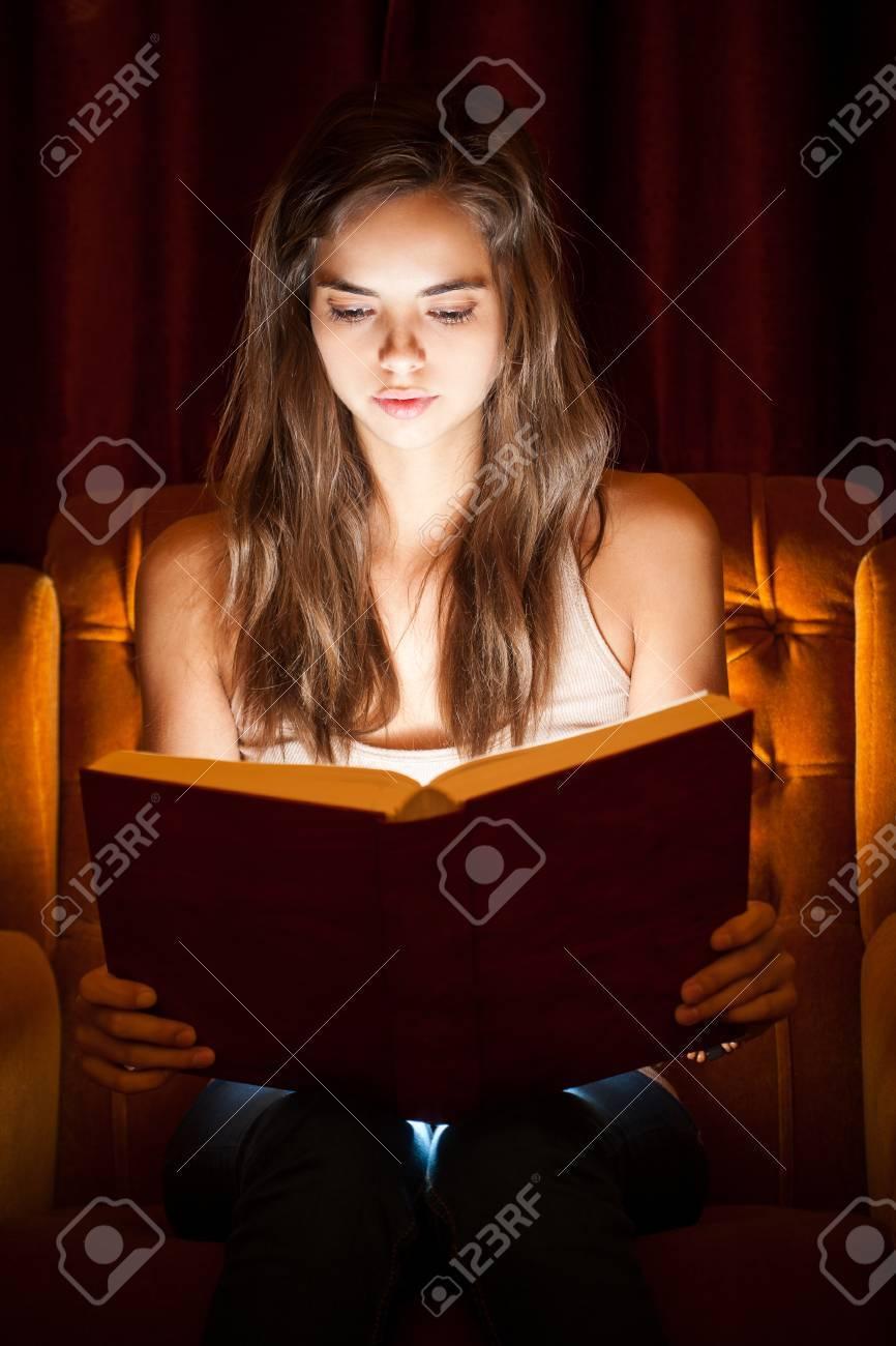 hermoso libro de lectura joven morena con la iluminacin creativa foto de archivo