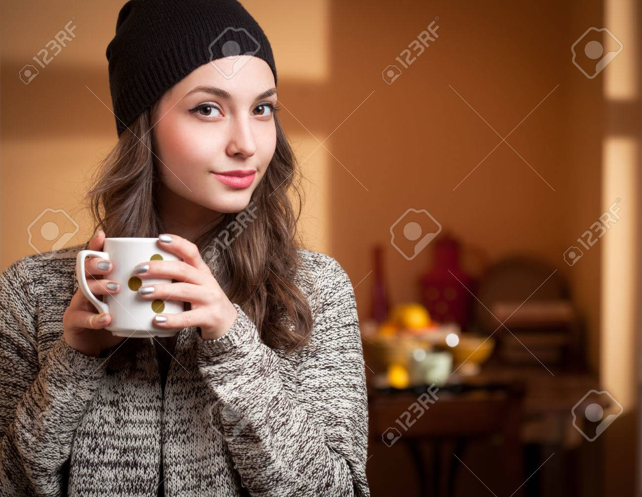 Portrait of a gorgeous young brunette relaxing with cup of hot beverage. - 38795821