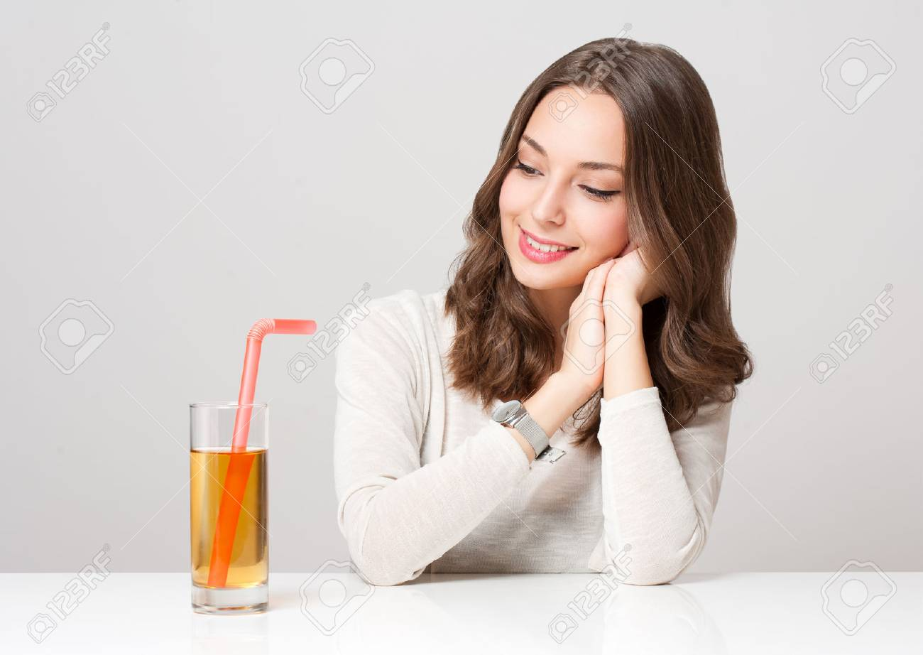 Studio portrait of a happy young brunette woman with glass of apple juice. - 51507050