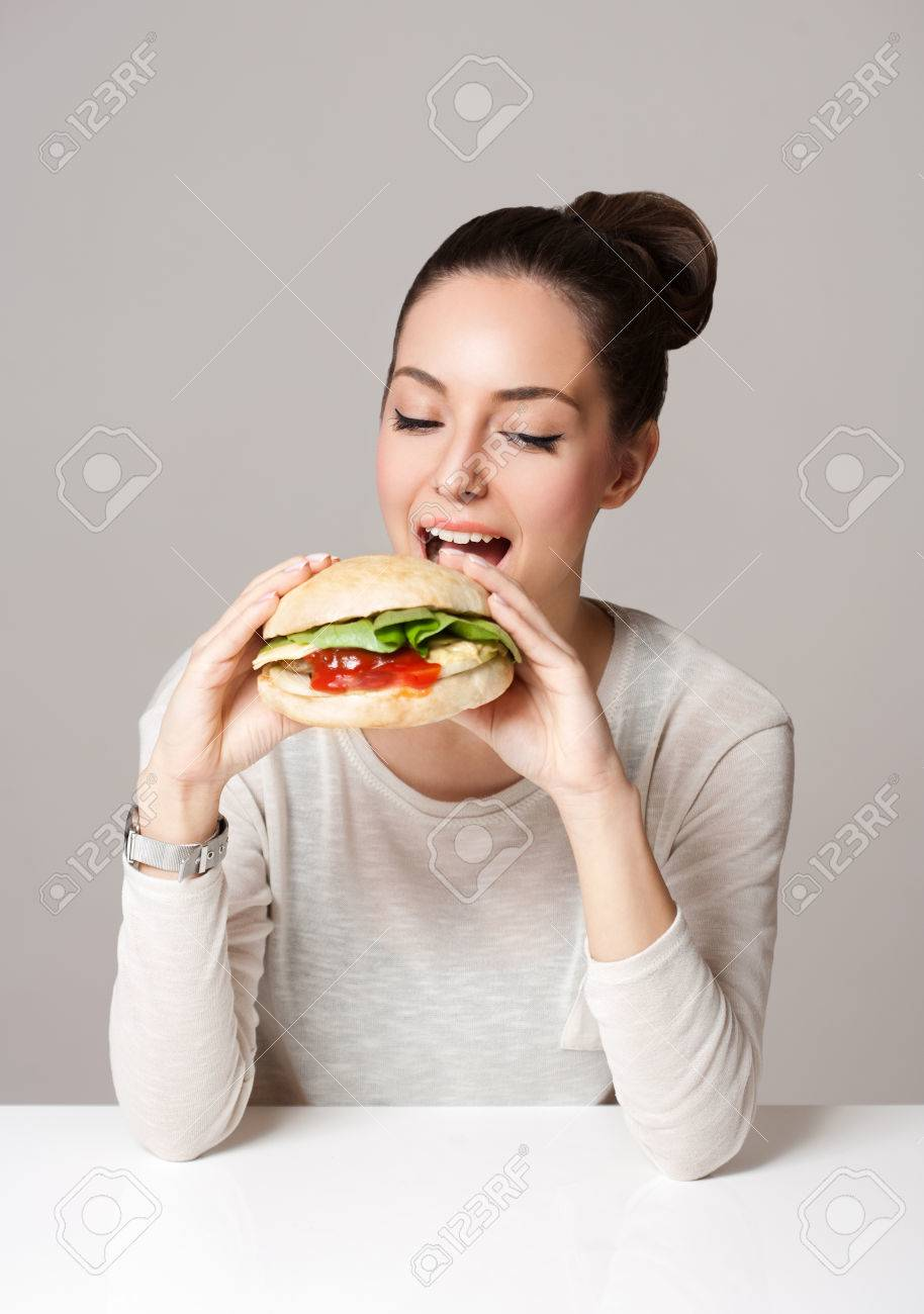 Portrait of a gorgeous young brunette woman showing diet food choices. - 53682847