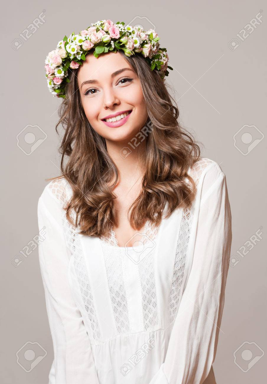 Portrait of a young spring beauty wearing flower wreath. - 55427847