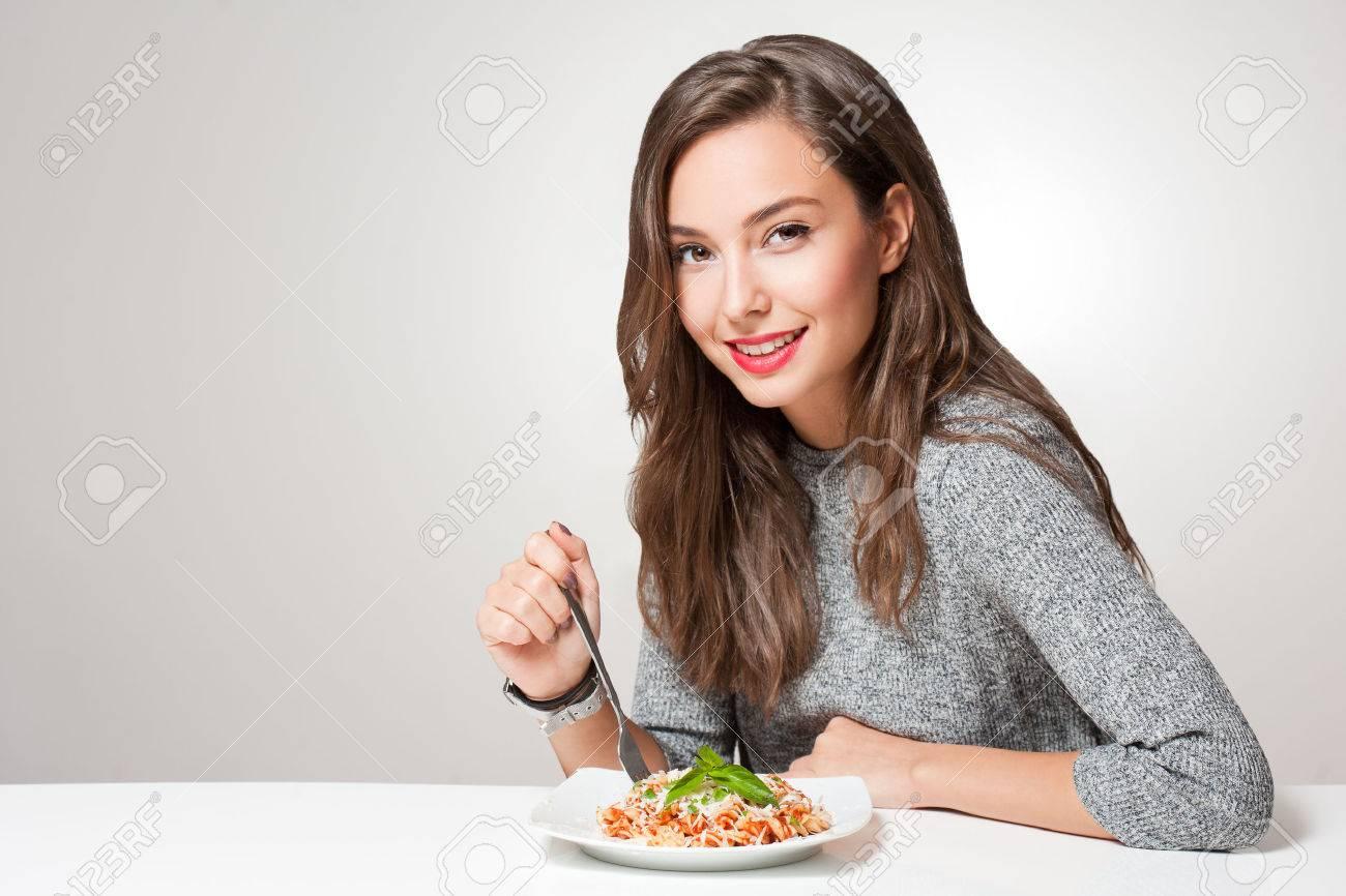 Beautiful young brunette woman eating Italian pasta. - 66081700