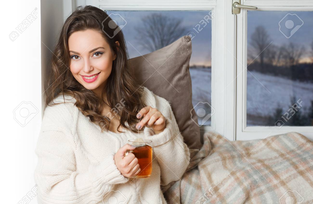 Gorgeous young brunette woman holding cup of hot beverage. Stock Photo -  95804995