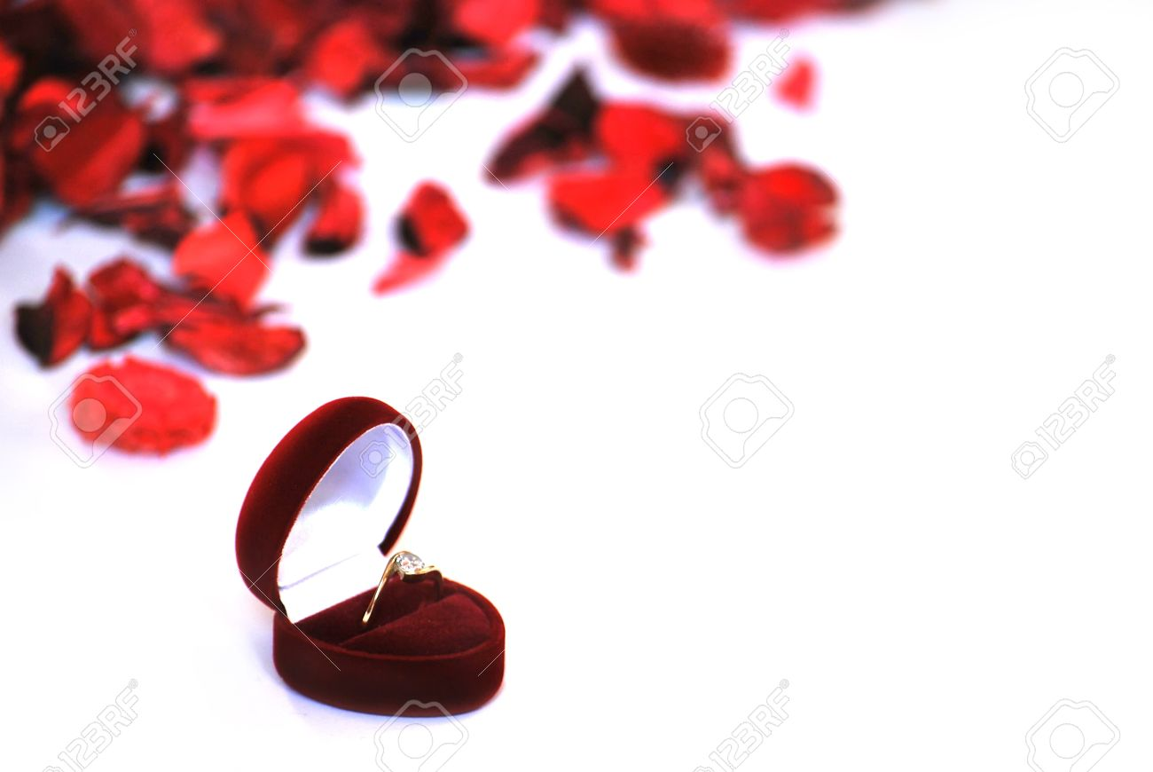 Engagement Ring In Red Box And Petals On White Background Stock