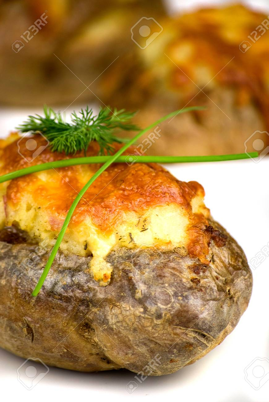 stuffed potatoes covered with cheddar cheese decorated with chives and dill leaves in a white plate Stock Photo - 12989758