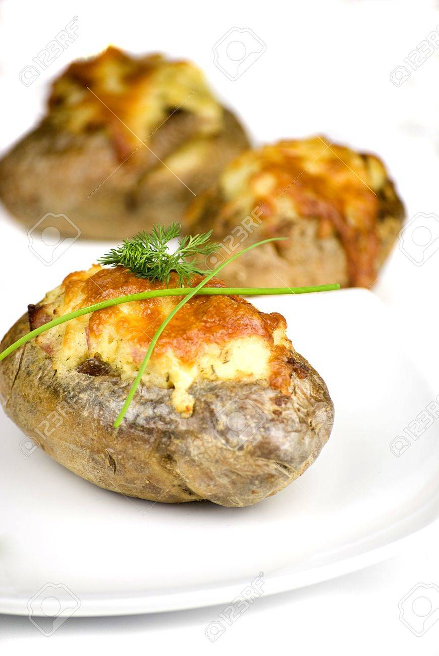 stuffed potatoes covered with cheddar cheese decorated with chives and dill leaves in a white plate Stock Photo - 13278146