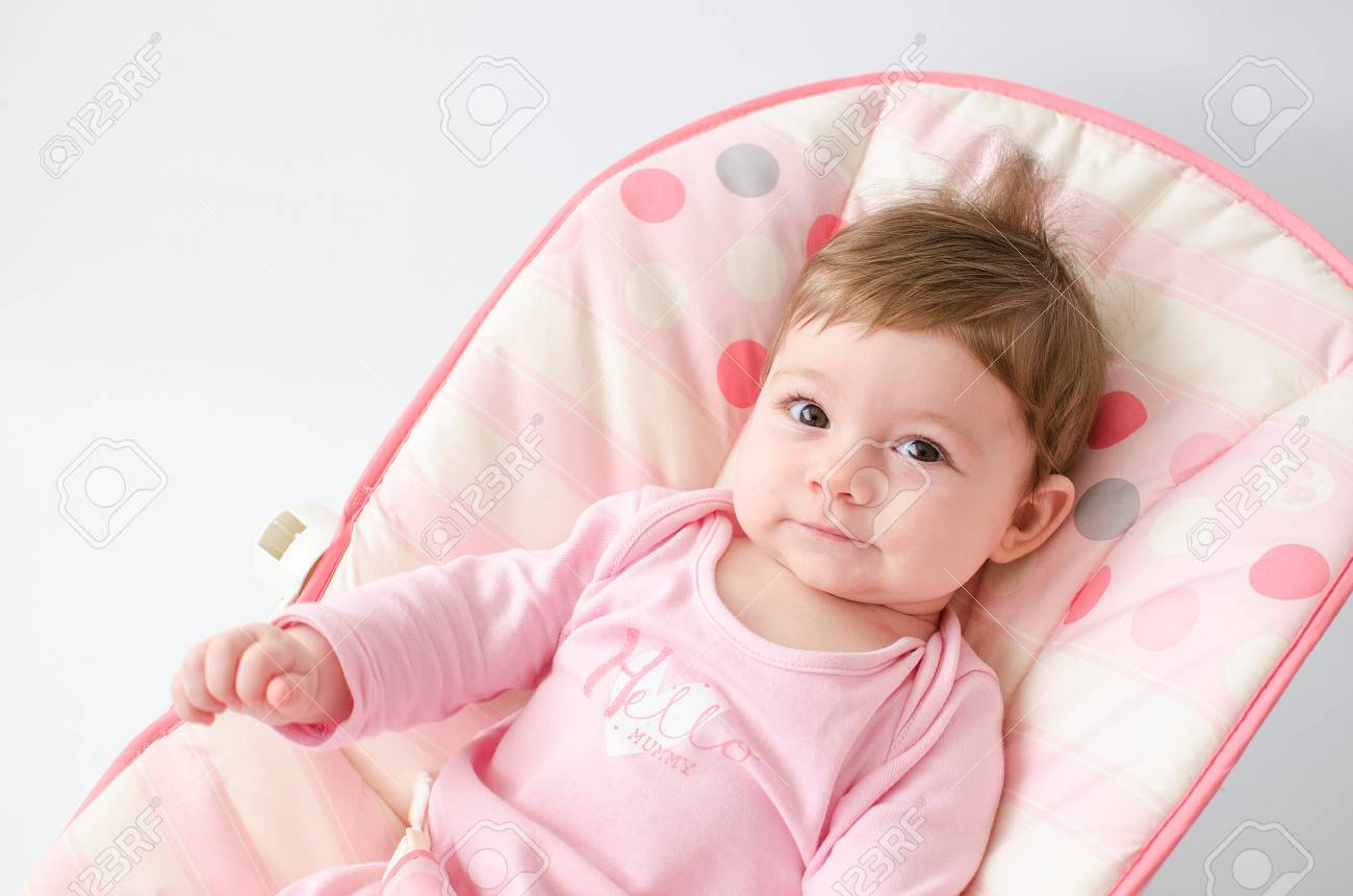 625bef2b7 Beautiful Happy Baby Girl In A Bouncer Wearing Pink Stock Photo ...