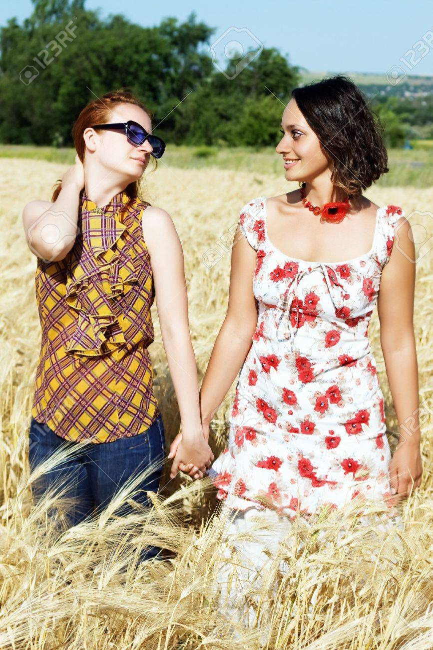 Two young girls in wheat field holding hands Stock Photo - 5111232