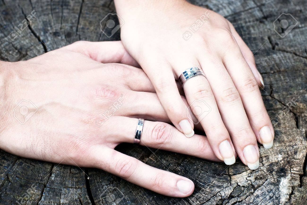 Two Hands With White Gold Wedding Rings On Stump Stock Photo