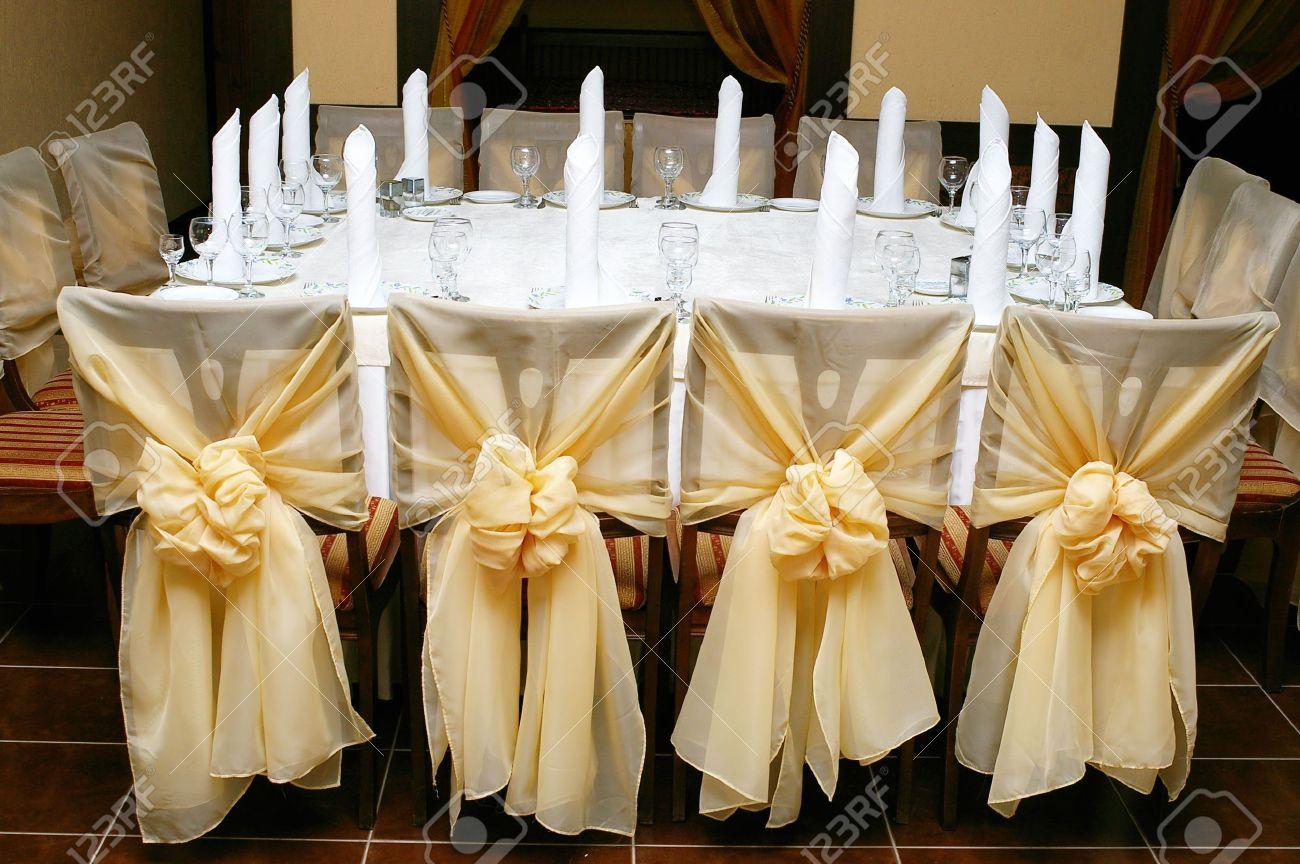 Stock Photo   Table Set For Wedding Reception With Golden Cloth Bows On Decorated  Chairs