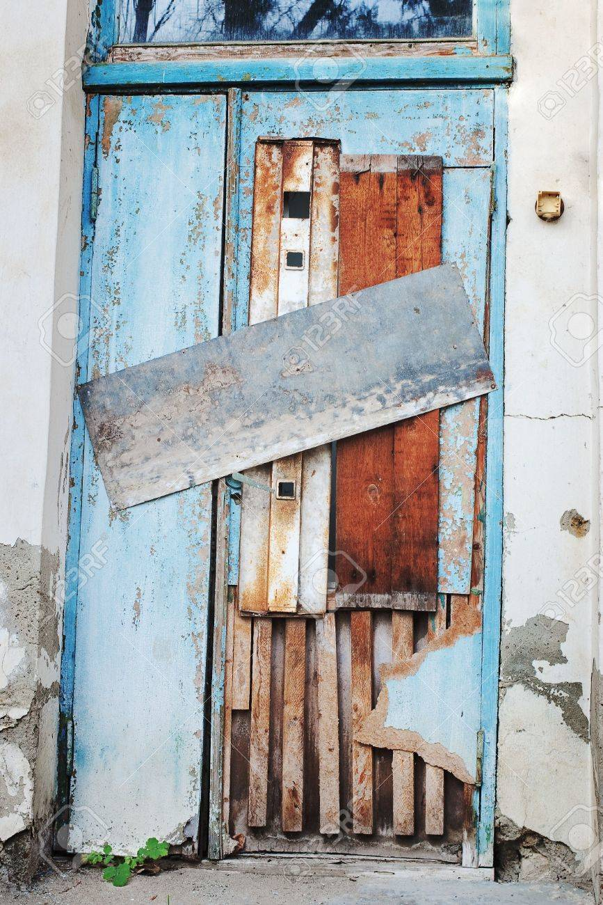 Old deserted blue door closed and boarded up by tin and wooden plates with green plant & Old Deserted Blue Door Closed And Boarded Up By Tin And Wooden ...