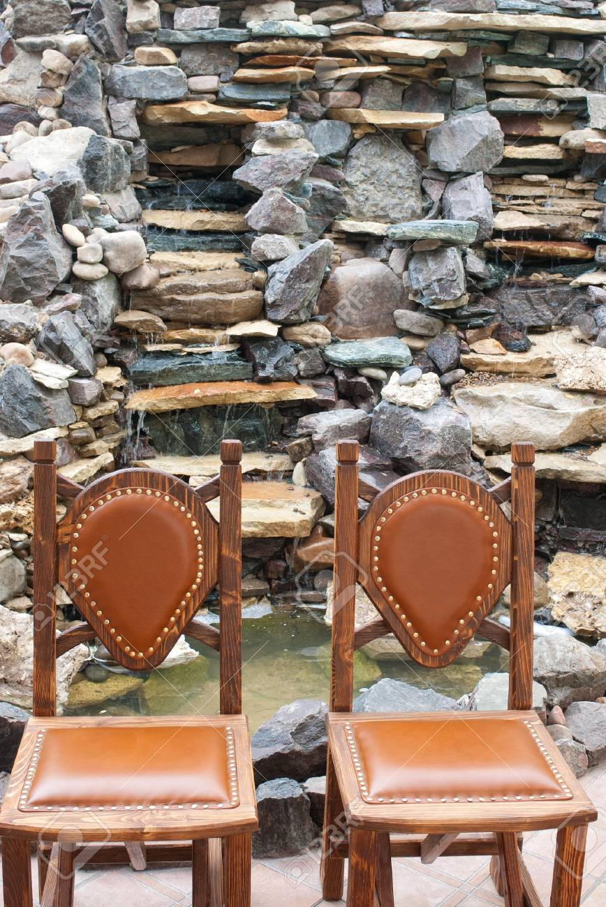 Stock Photo   Two Wooden Chairs With Straight Back Against Stone Decorated  Waterfall