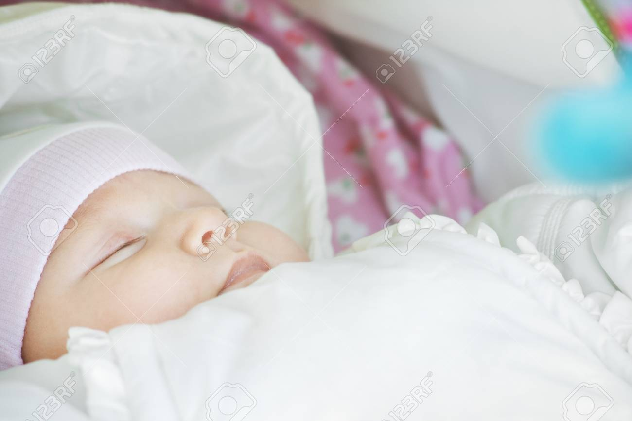 Closeup of sleeping baby dressed in white with shallow depth of field and copy space Stock Photo - 8337094