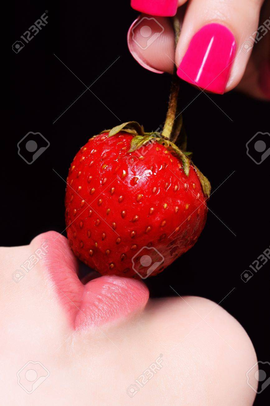 Closeup of young woman full lips with strawberry against black background with selective focus Stock Photo - 9663650