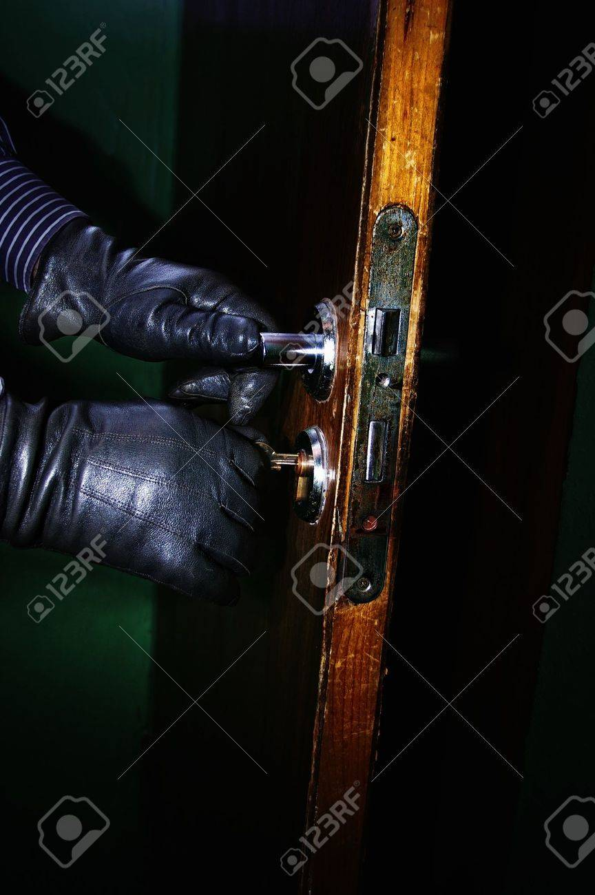 Closeup of burglar hands in leather gloves opening a door in the night with selective focus Stock Photo - 11066587