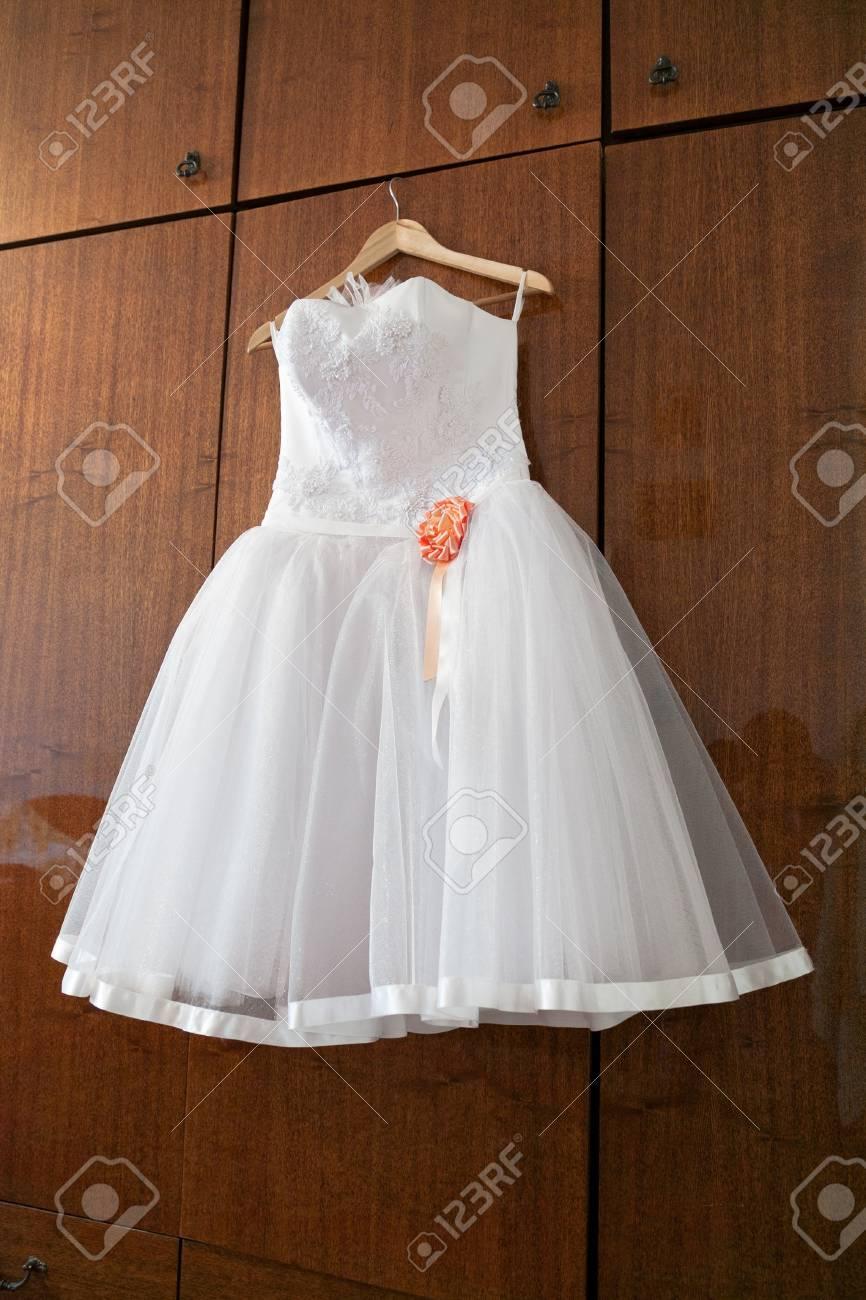 White Wedding Dress With Orange Bud On Hanger Stock Photo Picture