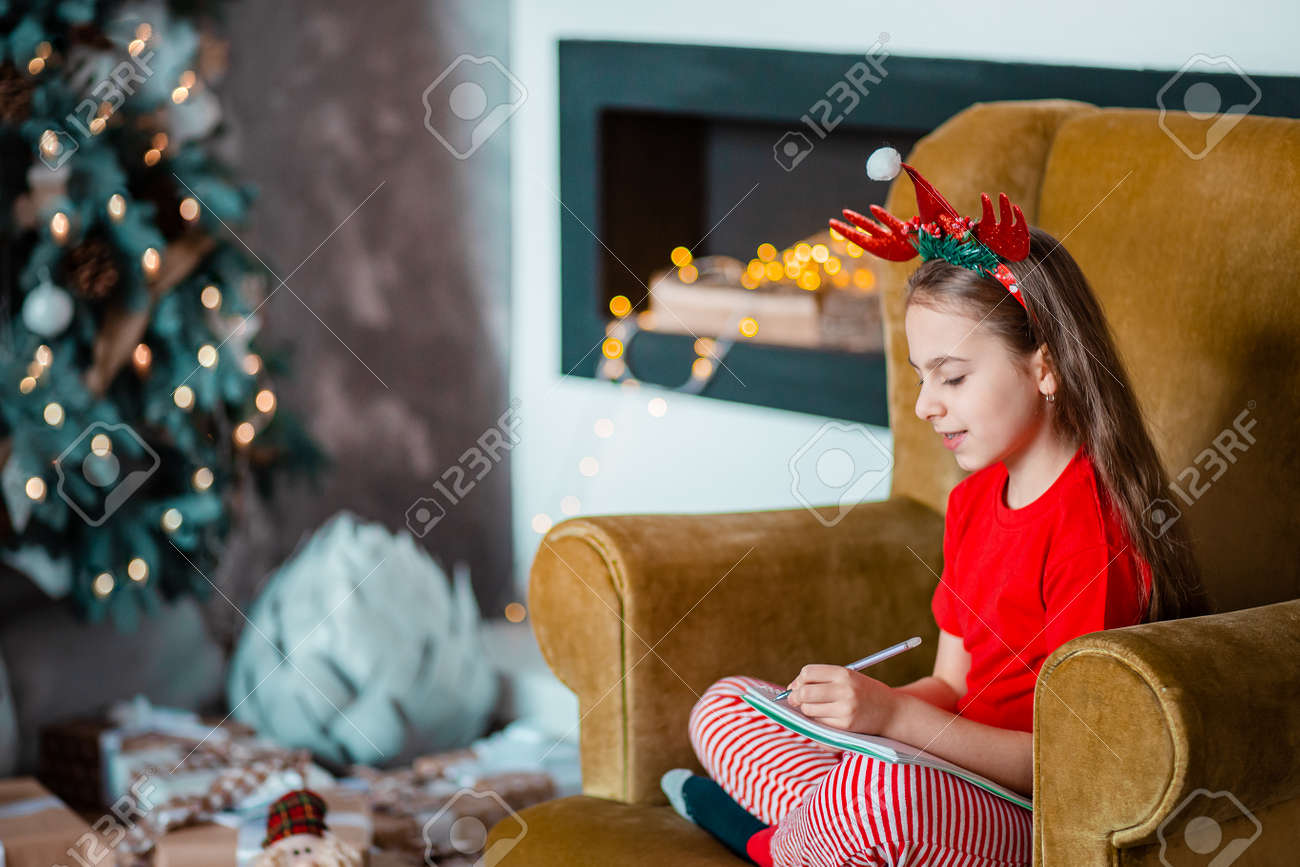 A cute girl in a Santa hat writes a letter to Santa near the Christmas tree. Happy childhood, a time for fulfilling desires. Merry Christmas. - 157538810