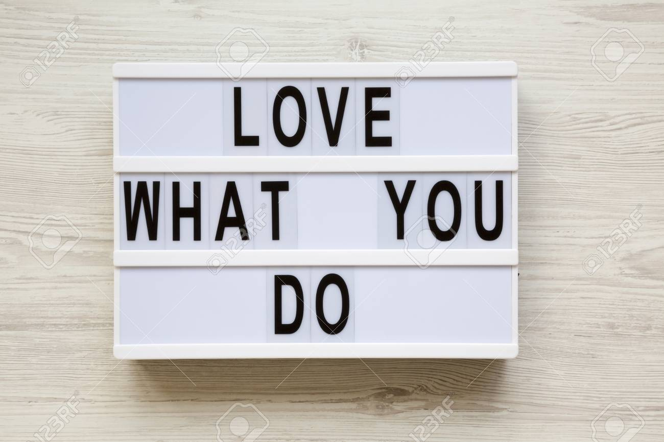 Lightbox with text 'Love what you do' over white wooden surface,