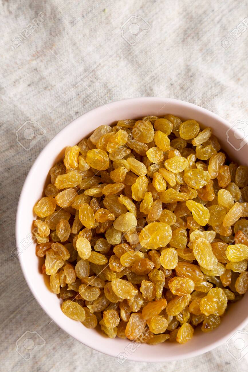 Golden Raisins in a Pink Bowl on cloth, top view. Flat lay, overhead, from above. Copy space. - 148240820