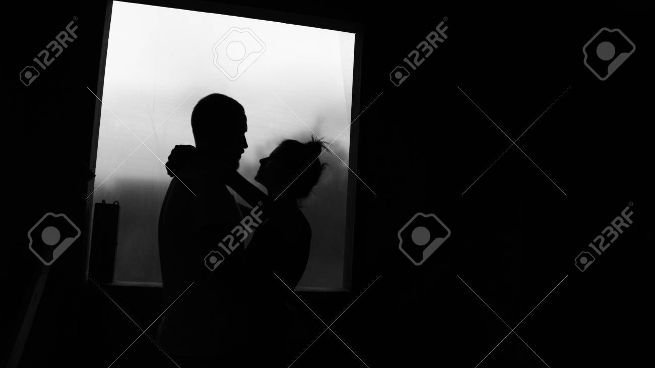 Lovers silhouettes couple against the window black and white photo stock photo 49174278