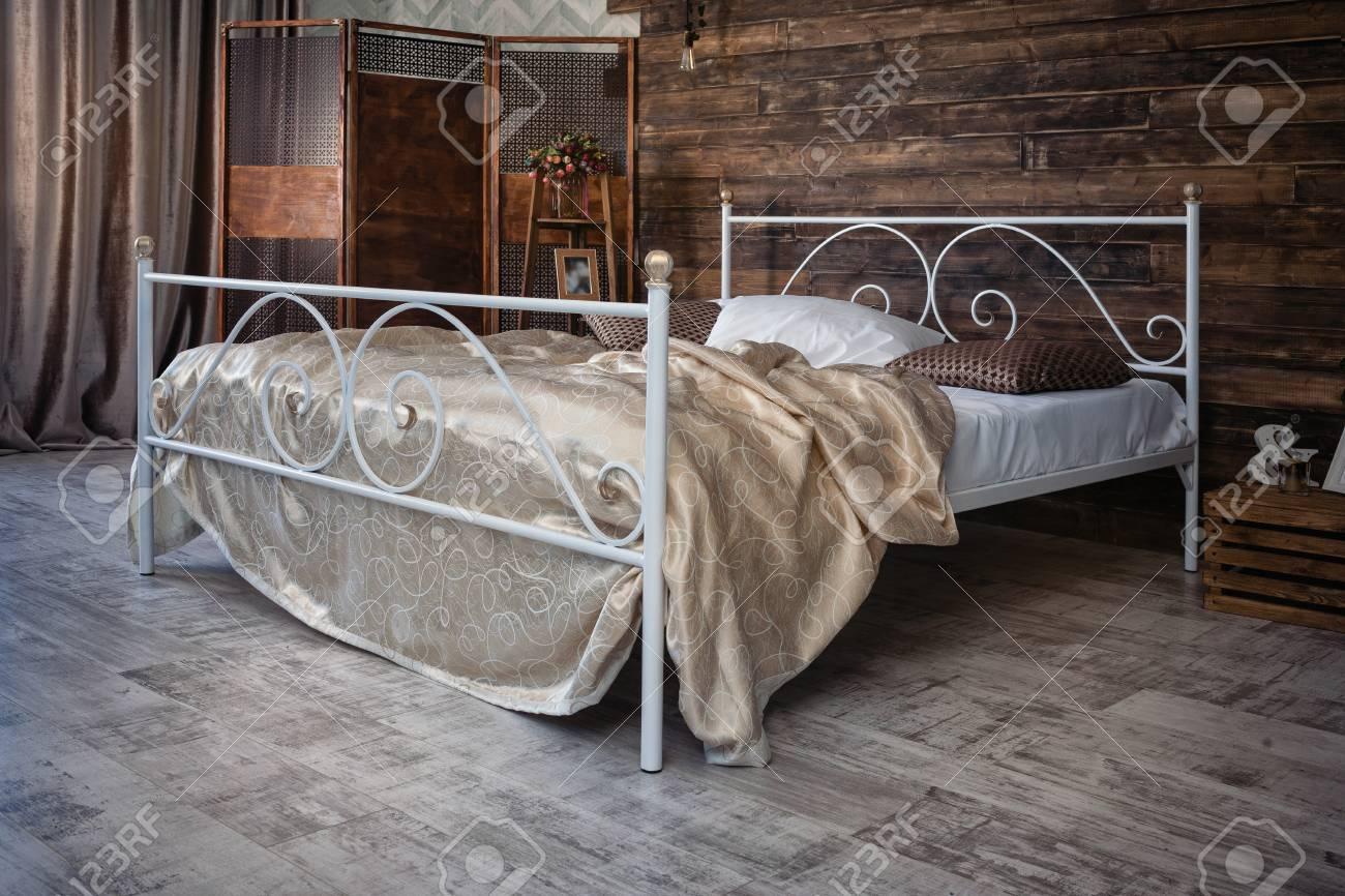 Grande letto matrimoniale in ferro battuto. Il letto è coperto con lenzuola  bianche