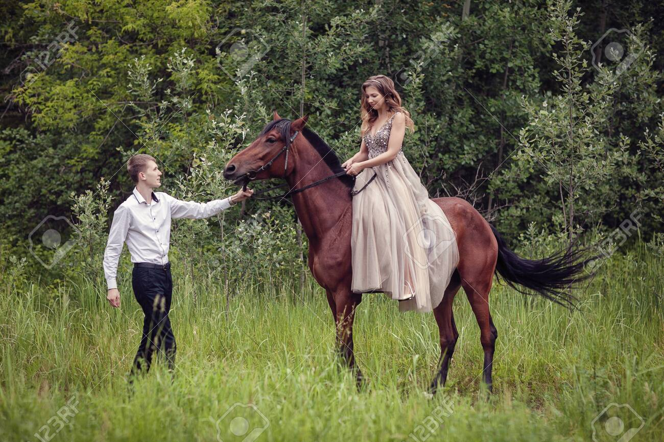 Love story. Two lovers in the forest. Photo with a bay horse. - 136597682