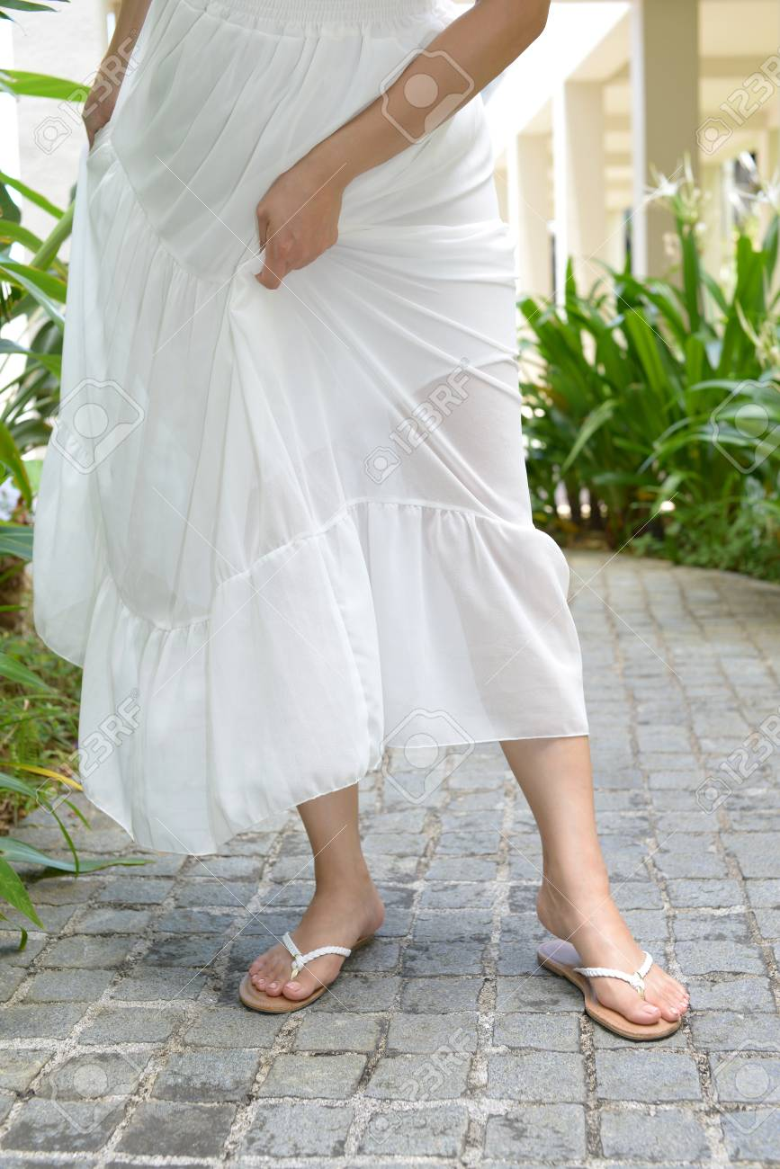 fb0888506 A woman in white dress wearing flip flops Stock Photo - 101806955