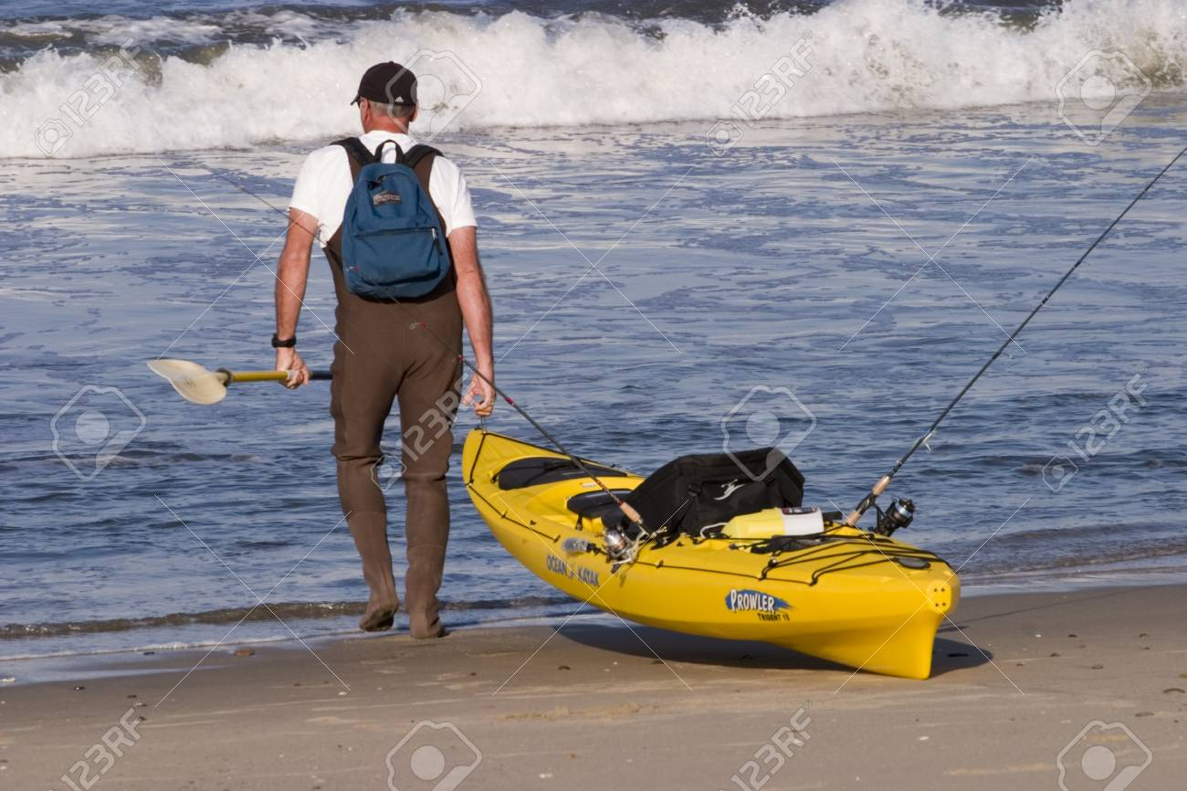 a sea kayaker and his yellow kayak getting ready to launch