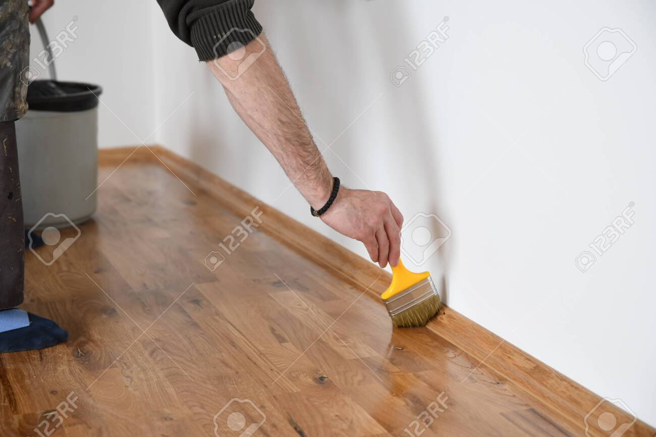 Lacquering Wood Floors Worker Uses A Brush To Coating Floors