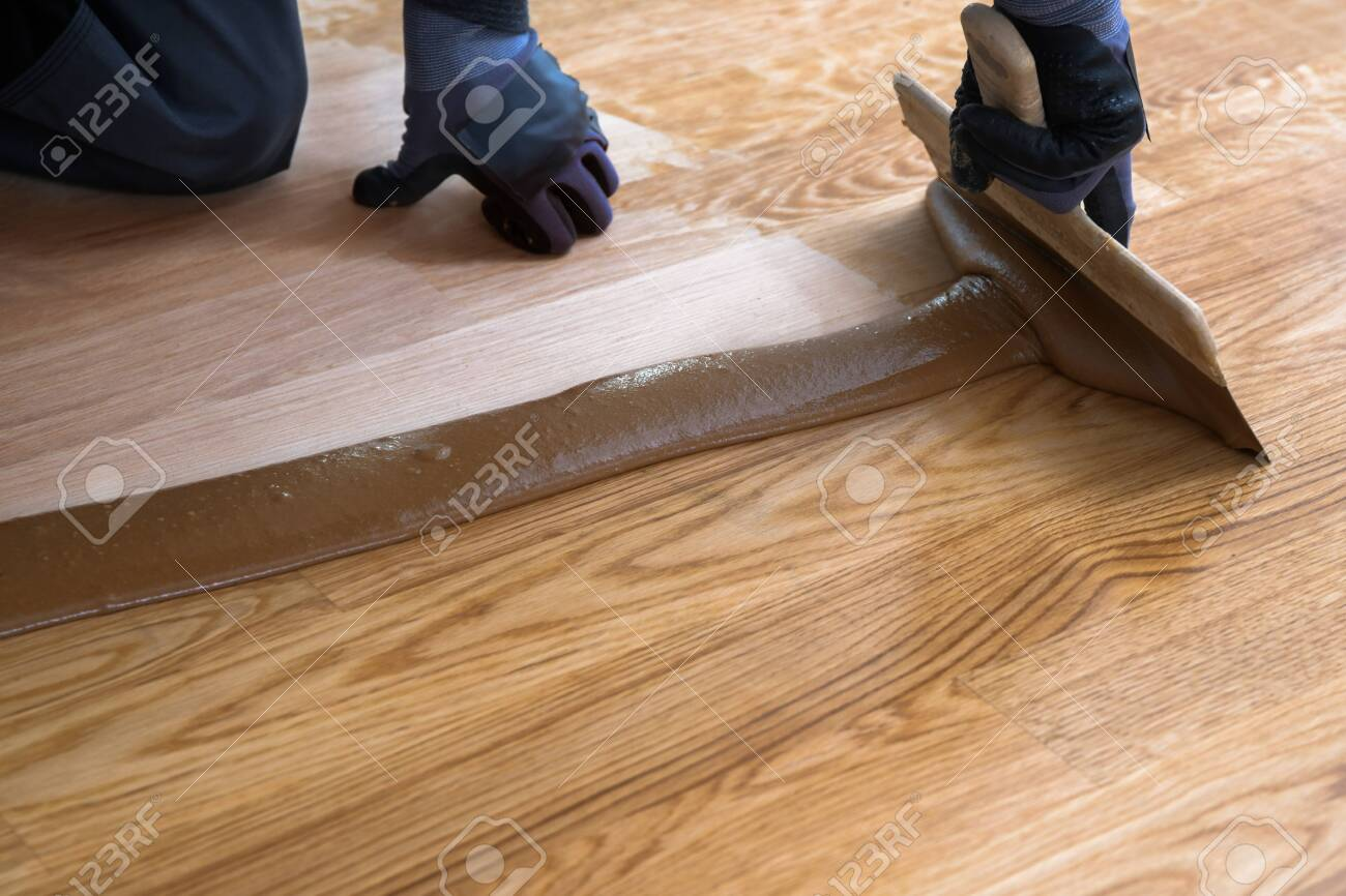 Carpenter Master With Gloves Grouting Wooden Parquet Phase After