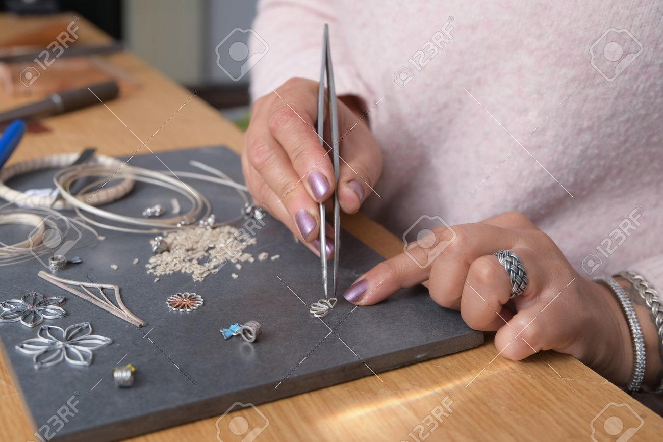 Woman - jeweler making jewellery in her small workshop - 162278884