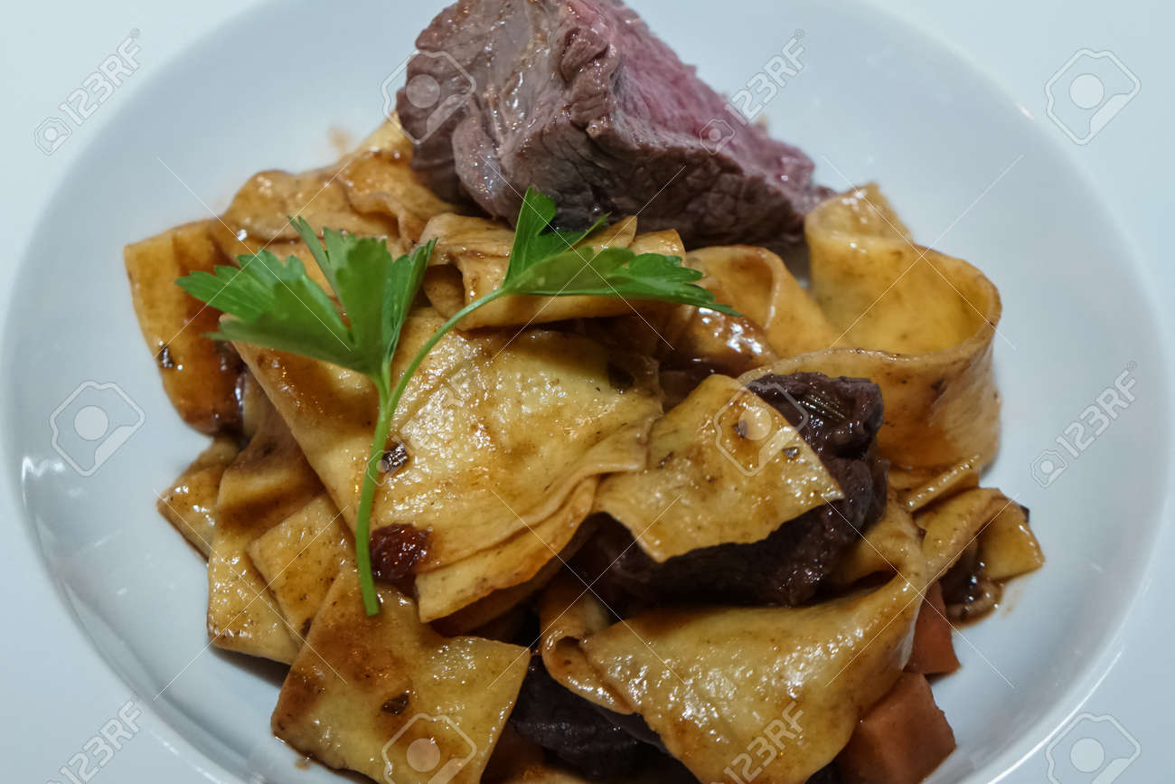 Baked pasta with sliced game meat seasoned with parsley, served on a plate - 163494955