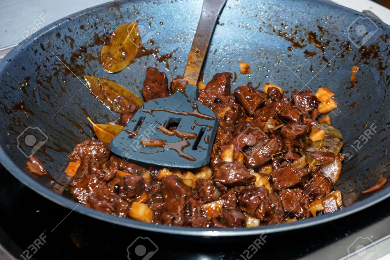 Fried meat in a frying pan closeup. ?eat in a pan fry - making food. Searing beef bottom round roast cubes in cast iron skillet - 163494959
