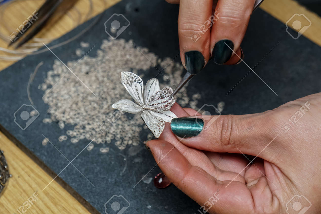 Process of making silver filigree. Production and making manufacturing, factory, cast craft design, process precious silver jewelry, filigree, ring jeweler, silversmith in workshop. - 163900454
