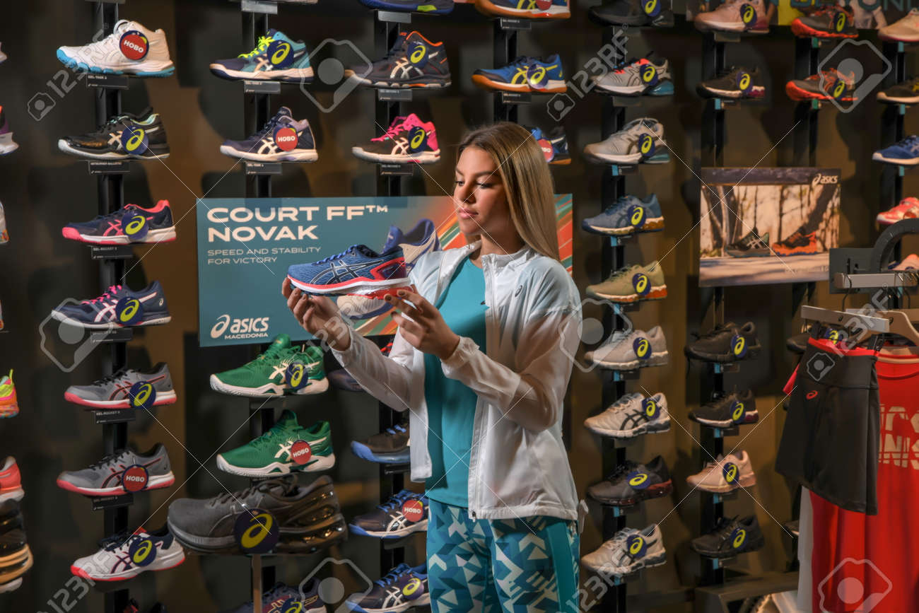 Skopje, Northern Macedonia - March 12, 2021: Asix store in Skopje, Northern Macedonia. Girl photo model wearing tracksuits and sneakers ASICS GEL, standing in her arms holding a new model of sneakers - 166164725