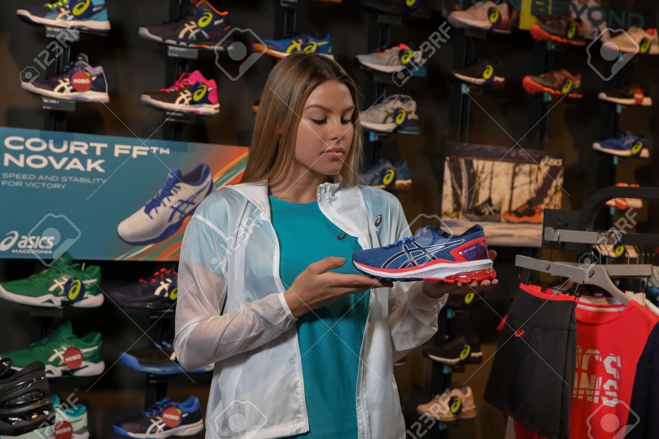 Skopje, Northern Macedonia - March 12, 2021: Asix store in Skopje, Northern Macedonia. Girl photo model wearing tracksuits and sneakers ASICS GEL, standing in her arms holding a new model of sneakers - 166164724