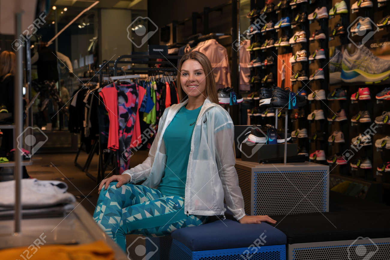 Skopje, Northern Macedonia - March 12, 2021: Asix store in Skopje, Northern Macedonia. Girl photo model dressed in sportswear and sneakers ASICS GEL, sitting and posing in a shop for sports equipment - 166164727