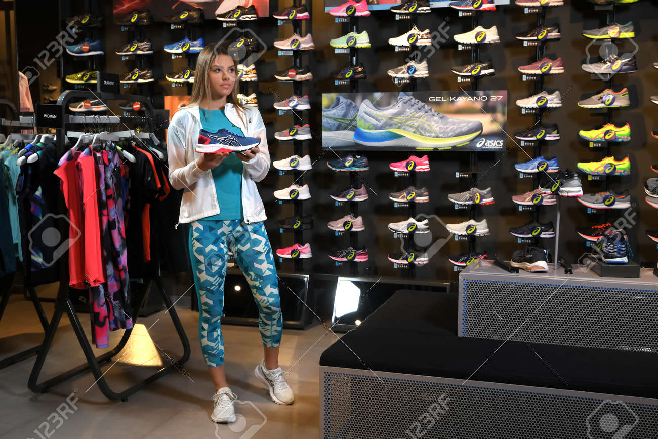 Skopje, Northern Macedonia - March 12, 2021: Asix store in Skopje, Northern Macedonia. Girl photo model wearing tracksuits and sneakers ASICS GEL, standing in her arms holding a new model of sneakers - 166164717