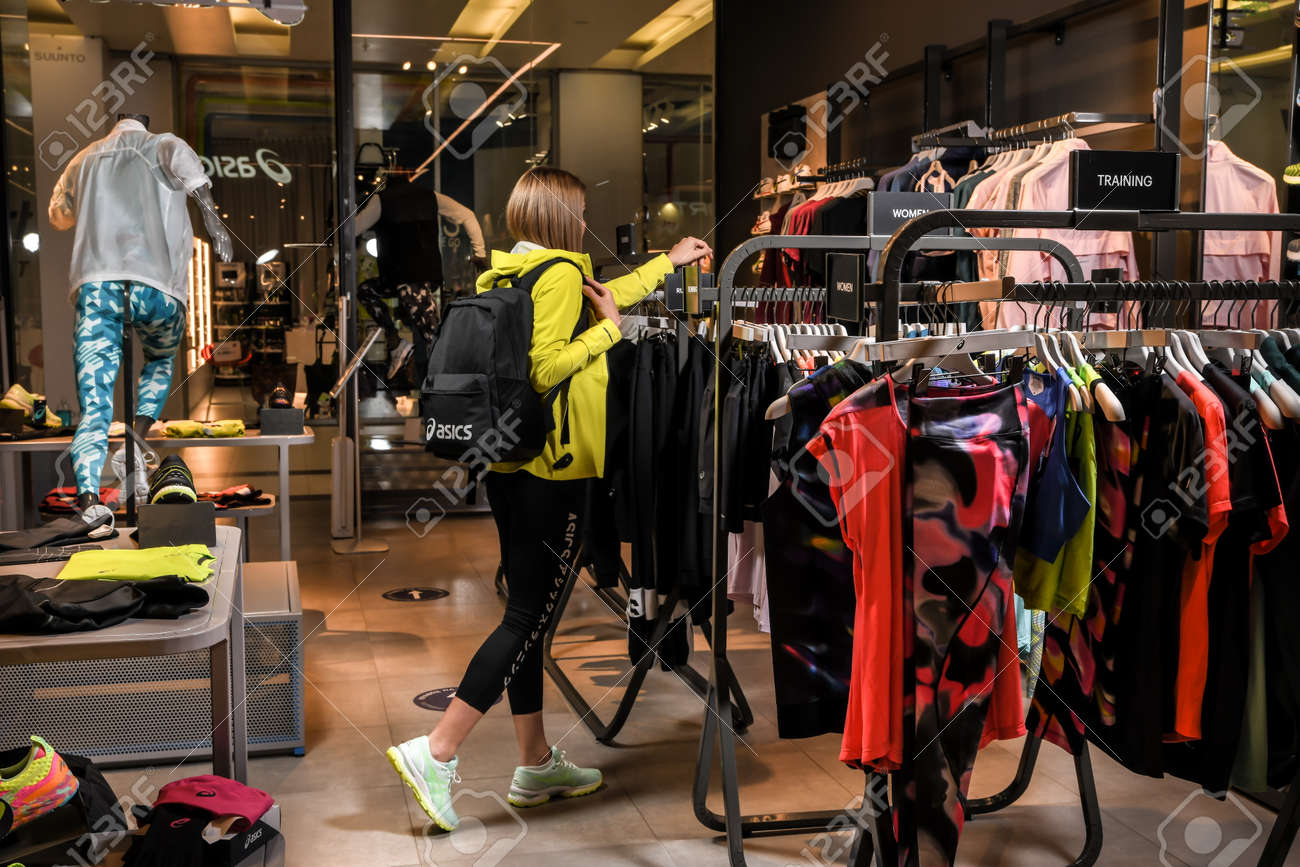 Skopje, North Macedonia - March 12, 2021: Asics store in Skopje, North Macedonia. Girl photo model wearing sports tracksuits and sneakers ASICS GEL, carrying a sports backpack on her shoulder - 166241078