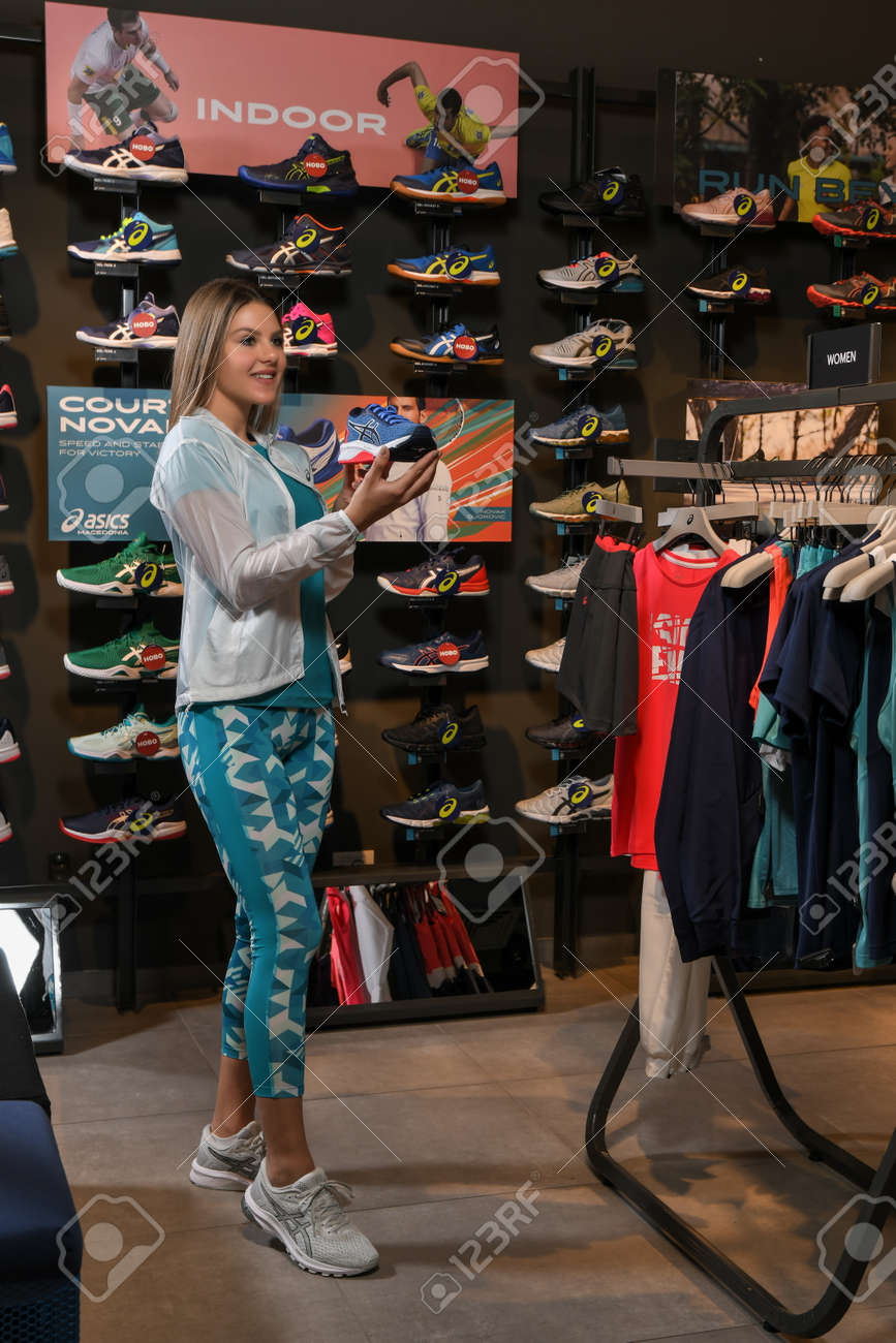 Skopje, Northern Macedonia - March 12, 2021: Asix store in Skopje, Northern Macedonia. Girl photo model wearing tracksuits and sneakers ASICS GEL, standing in her arms holding a new model of sneakers - 166164698