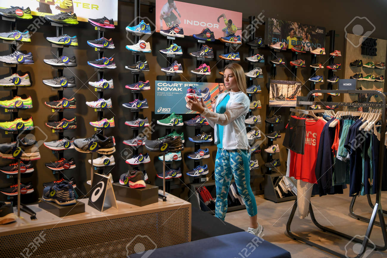 Skopje, Northern Macedonia - March 12, 2021: Asix store in Skopje, Northern Macedonia. Girl photo model wearing tracksuits and sneakers ASICS GEL, standing in her arms holding a new model of sneakers - 166164726