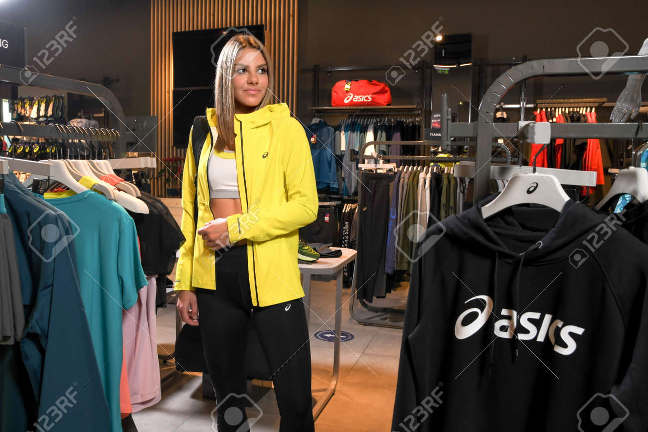 Skopje, North Macedonia - March 12, 2021: Asics store in Skopje, North Macedonia. Girl photo model wearing sports tracksuits and sneakers ASICS GEL, carrying a sports backpack on her shoulder - 166164722