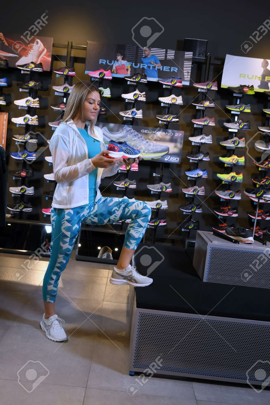 Skopje, Northern Macedonia - March 12, 2021: Asix store in Skopje, Northern Macedonia. Girl photo model wearing tracksuits and sneakers ASICS GEL, standing in her arms holding a new model of sneakers - 166164703