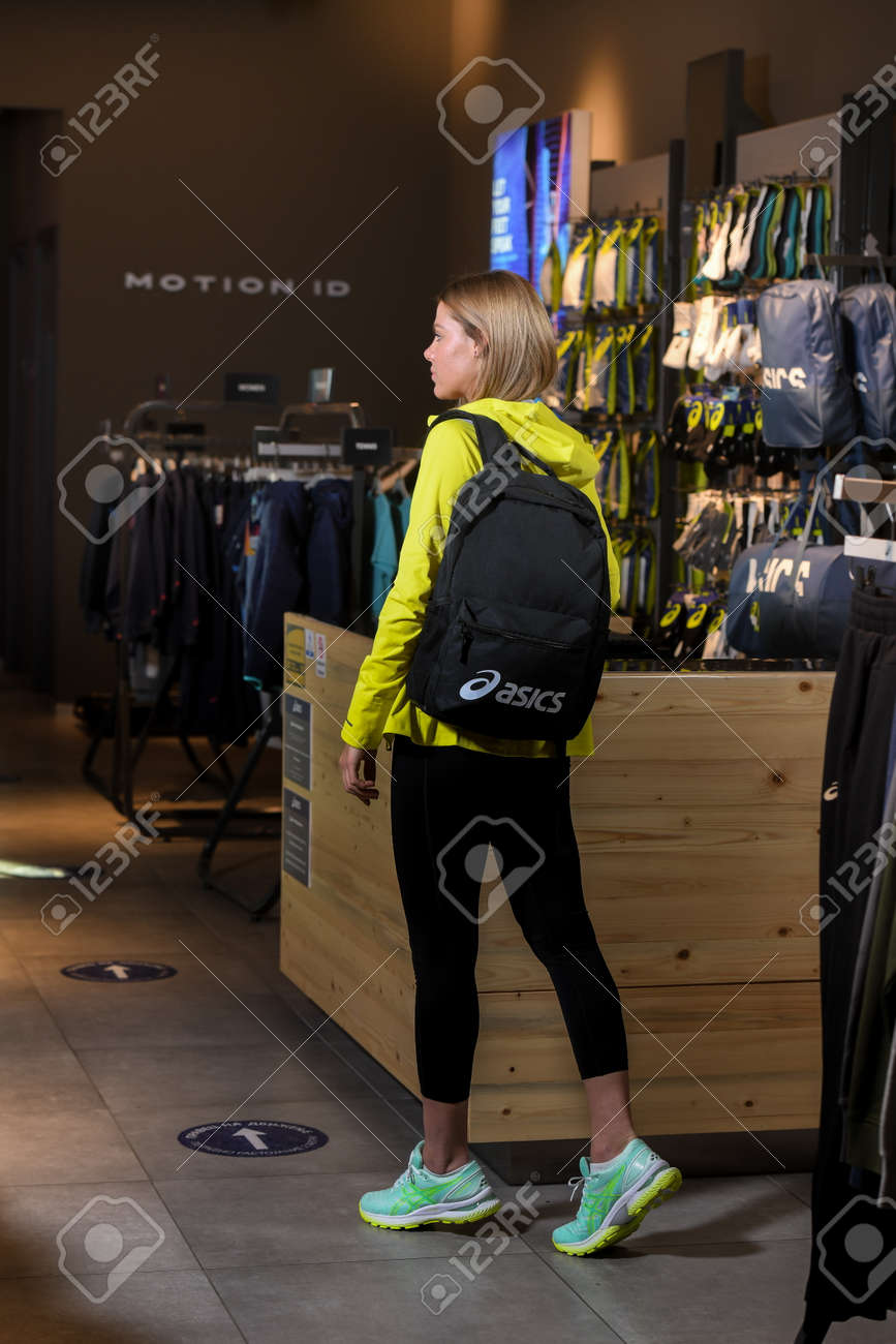 Skopje, North Macedonia - March 12, 2021: Asics store in Skopje, North Macedonia. Girl photo model wearing sports tracksuits and sneakers ASICS GEL, carrying a sports backpack on her shoulder - 166321432