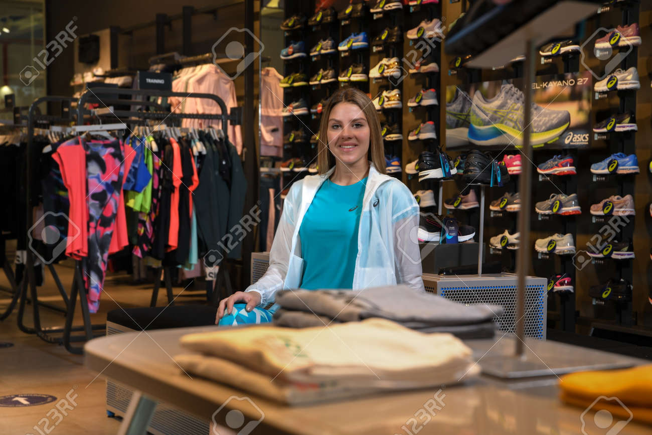 Skopje, Northern Macedonia - March 12, 2021: Asix store in Skopje, Northern Macedonia. Girl photo model dressed in sportswear and sneakers ASICS GEL, sitting and posing in a shop for sports equipment - 166164690