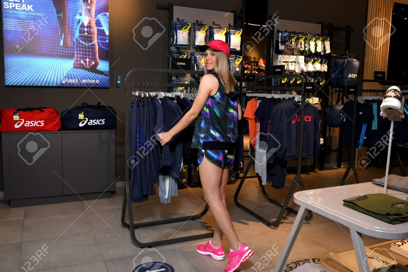 Skopje, Northern Macedonia - March 12, 2021: Asics store in Skopje, Northern Macedonia. Girl photo model wearing sports panties, T-shirt, hat and sneakers ASICS GEL, standing posing in a sports shop - 166164697