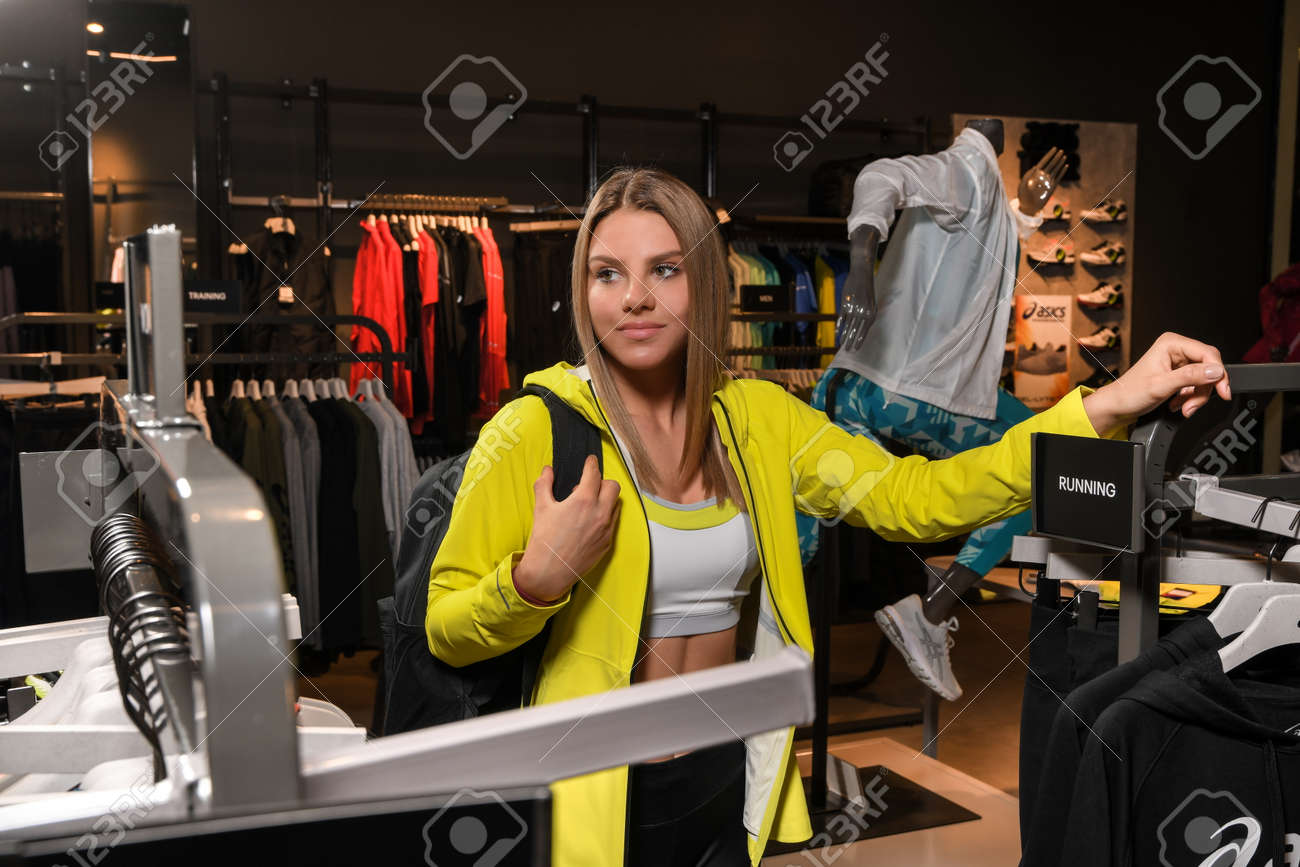 Skopje, North Macedonia - March 12, 2021: Asics store in Skopje, North Macedonia. Girl photo model wearing sports tracksuits and sneakers ASICS GEL, carrying a sports backpack on her shoulder - 166164685