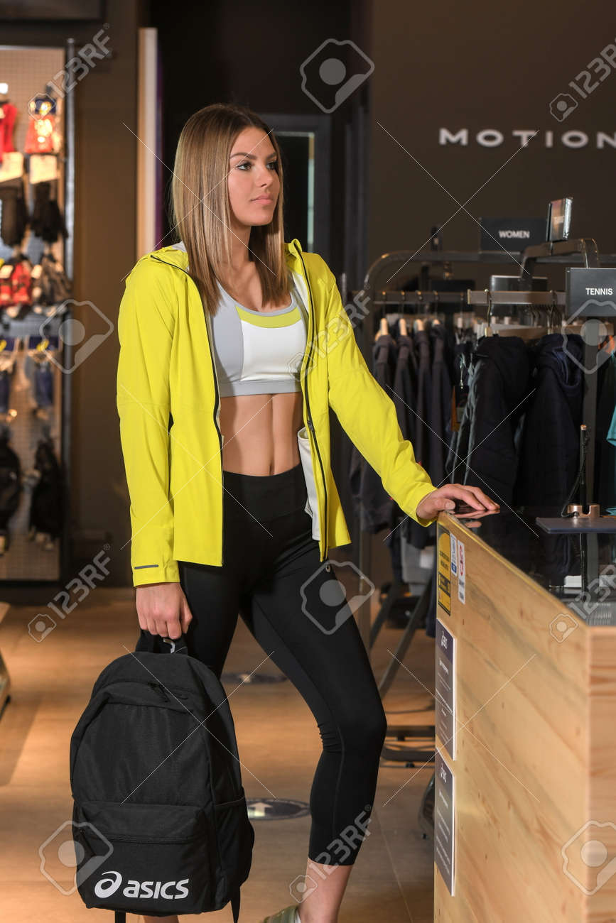 Skopje, North Macedonia - March 12, 2021: Asics store in Skopje, North Macedonia. Girl model wearing sports tracksuits and sneakers ASICS GEL, holding a sports backpack - 166164713